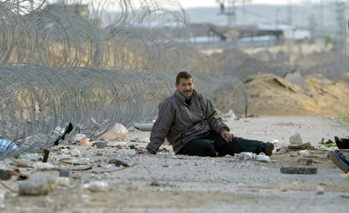A Palestinian worker waits to go to work in Israeli controlled industrial zone in Erez area between ...