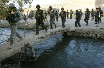 Afghan soldiers led by U.S. Army Major Jameson Kirby patrol a village in Baluchi Pass in Uruzgan province