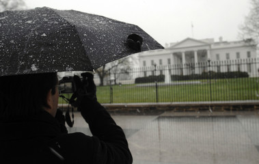 A light snow settles on a tourist's umbrella as he takes a picture of the White House in Washington