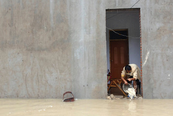 A woman clears water from her house to a flooded street in Zhuangmu County