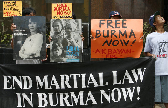 Protesters hold pictures democracy icon Aung San Suu Kyi during a protest in front of the Myanmar embassy in Manila's financial district of Makati