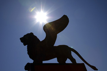 Golden lion, symbol of Venice Film Festival, is silhouetted against sun in Venice