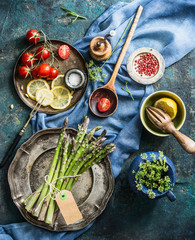 Asparagus cooking preparation with ingredients and cooking spoon on rustic kitchen table background, top view. Healthy seasonal food or vegetarian eating concept