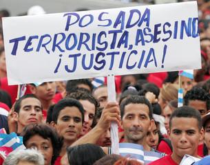 "Cubans hold a placard that reads ""Posada terrorist, murderer justice"" in Havana."