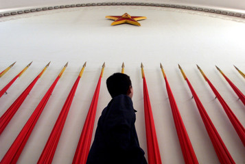 A Chinese elementary school student looks up at a symbol of the People's Liberation Army while visit..
