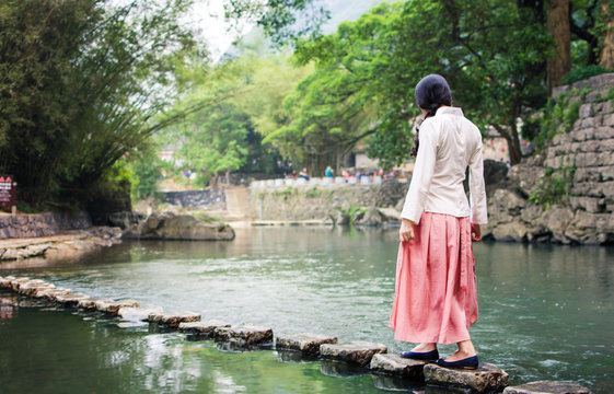 Girl walking on the stone bridge in the river