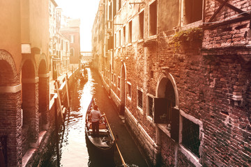 Beautiful Sunset View on Venetian Water Channel with Gondolier and Boat. Venice, Italy.