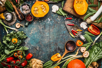 Healthy and organic harvest vegetables and ingredients: pumpkin, greens, tomatoes,kale,leek,chard,celery on rustic kitchen table background for tasty Thanksgiving seasonal cooking, frame, top view Wall mural