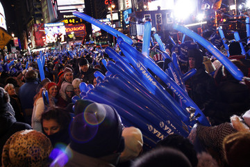 Revelers receive balloons as they pack Times Square during the New Year's Eve celebration in New York