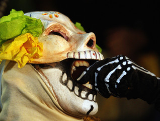 A woman dressed as a skeleton bites into a candy skull during festivities for 'Dia De Los Muertos' in Los Angeles