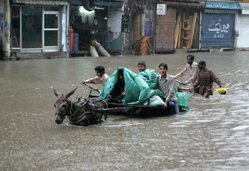 A donkey cart owner drives through a flooded street after heavy downpour in Lahore