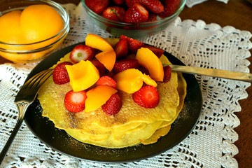 Stack of sweet pancakes with strawberries, apricot and cinnamon sugar