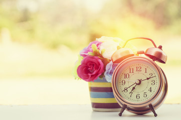 alarm clock with flower on wood table and copy space
