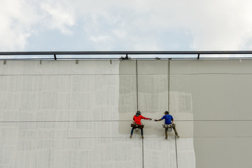 Un safety Painters and harnesses hanging high building in construction site,hand brush color work concept
