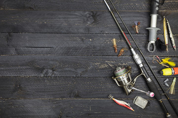 spinning rod and reel, fishing tackle on black wooden background.