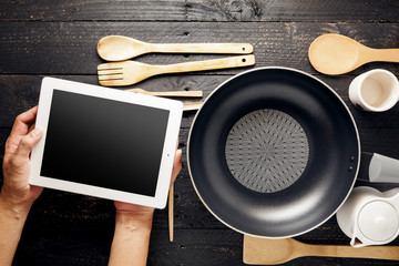 Hand use tablet with kitchenware on black wood table,concept searching the cooking menu.