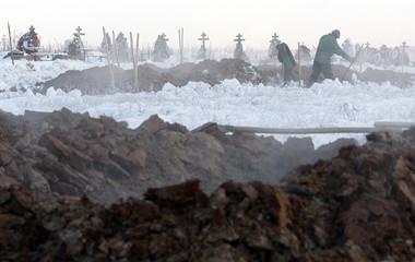 Workers dig graves for today's burial at a cemetery outside Perm