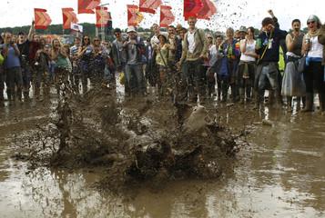 A reveller slides in the mud during the Glastonbury music festival