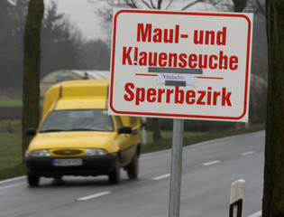 A CAR DRIVES PASSED A WARNING SIGN FOR FOOT AND MOUTH DISEASE IN HOLTUM MARSCH.