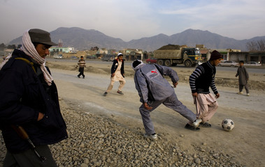 A policeman watches as boys play soccer in a street in Kabul
