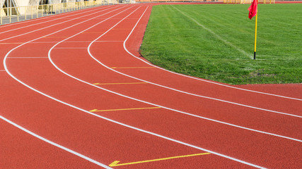 Red running track and white lanes on sport stadium