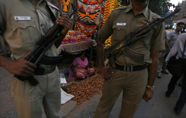 Policemen stand guard at a crowded market place in Delhi
