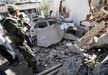 A gendarme looks at damaged cars at the site of a blast outside a police station in Tizi Ouzou