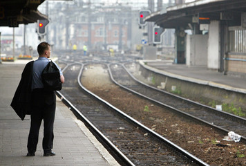 PASSENGER WAITS ON EMPTY PLATFORM DURING RAIL WORKERS STRIKE ATBRUSSELS STATION.