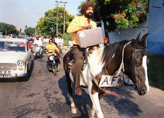 INDIAN SATIRIST AND COMEDIAN JASPAL BHATTI RIDES A HORSE IN A COMIC PROTEST IN CHANDIGARH.