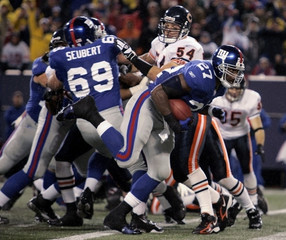 New York Giants Jacobs scores touchdown past teammate Seubert and Chicago Bears Urlacher during first quarter NFL football game in East Rutherford