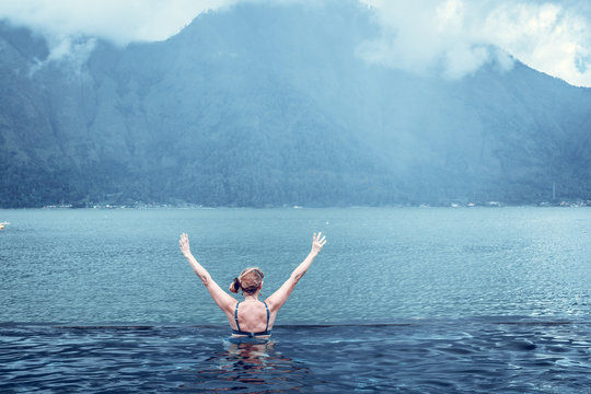 Senior woman in the nature swimming pool with amazing mountain background. Tropical island Bali, Indonesia.