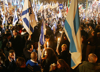 Protesters hold candles and Israeli flags near the Iranian embassy in Rome