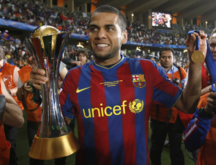 Barcelona's Alves holds the trophy after defeating Estudiantes' in their FIFA Club World Cup final soccer match in Abu Dhabi