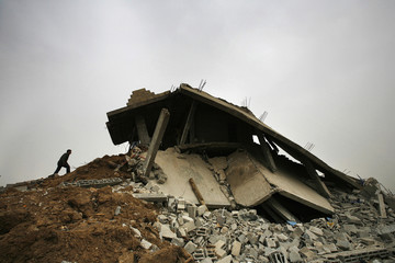 A palestinian youth climbs onto his destroyed home in Gaza