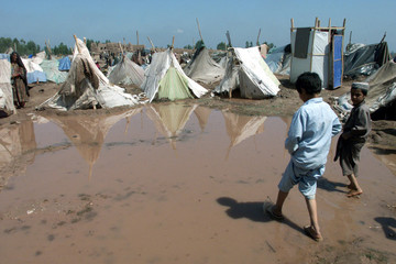 AN AFGHAN BOY WALKS THROUGH A FLOODED AREA IN AN AFGHAN REFUGEE CAMP IN JALLOZAI.