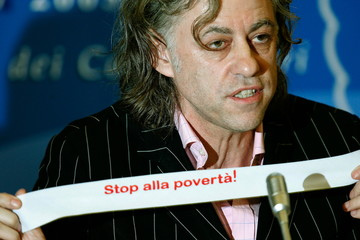 """Irish rock star Bob Geldof shows a sticker reading in Italian """"Stop poverty"""" during a news conferenc.."""