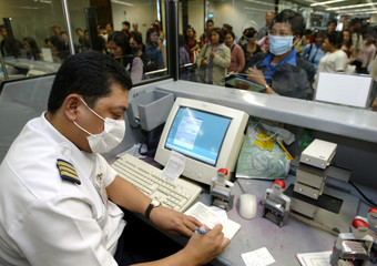 A PHILIPPINE IMMIGRATION OFFICER WEARS A SURGICAL MASK AT MANILAAIRPORT.