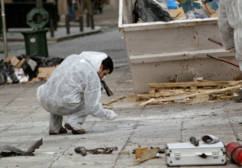 A forensic expert scours through debris after morning bomb blast in Athens