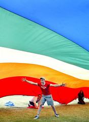 GAY RIGHTS SUPPORTER CELEBRATES UNDER PRIDE FLAG.