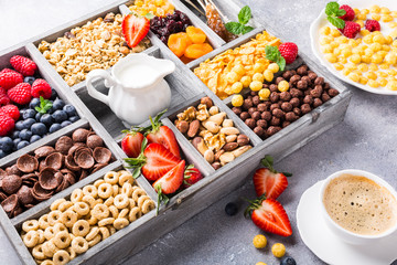 Healthy breakfast with coffee, variety of cold quick cereals and berries in old gray wooden box, selective focus.
