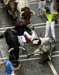 RUNNERS SCRAMBLE AS FIGHTING BULLS CHARGE ALONG STREET DURING THE 8THAND LAST RUN IN PAMPLONA.