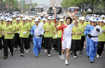 South Korean actor Song Il-gook runs with plainclothes policemen during the Beijing Olympic torch relay in central Seoul