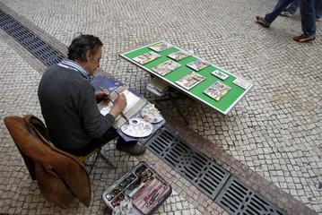 An artist paints tiles in town centre of Lisbon