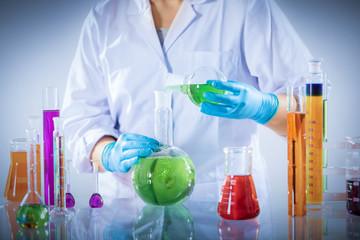 Laboratory worker mixes chemical liquid sample.