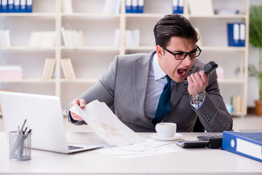 Businessman spilling coffee on important documents