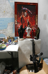An AR-15 rifle is seen at base of altar inside house seized by army during operation in Monterrey