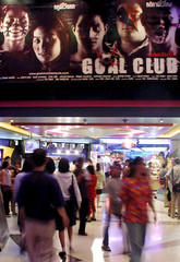 MOVIEGOERS WALK UNDER A POSTER FOR A THAI MOVIE IN BANGKOK.