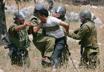 Israeli troops detain a Palestinian demonstrator in Bilin