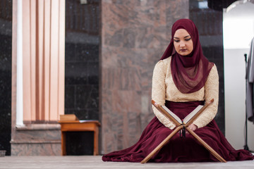 Young and beautiful girl sitting covered in sumptuous dress and teaches the Quran which is located on a wooden rack in front of her