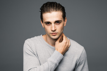 Portrait of a smart serious handsome young man standing against grey background